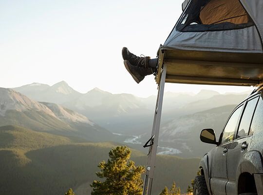 Someone enjoying camping in their car-top tent.