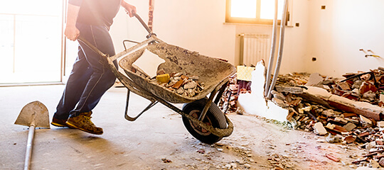 A wheelbarrow being pushed through a room in a home.