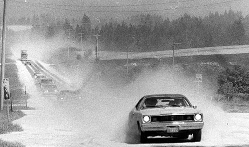 Cars raise ash clouds while driving roads following the 1980 eruption of Mount St. Helens