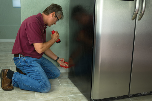 man holding flashlight inspects floor behind refrigerator