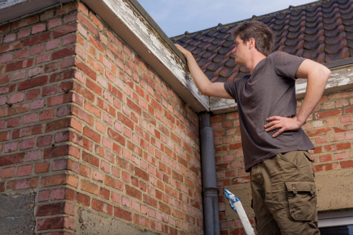 young man inspects edge of roof on old brick house