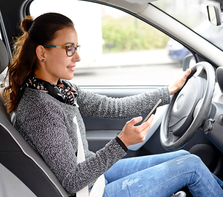 woman testing on hand held phone while driving car
