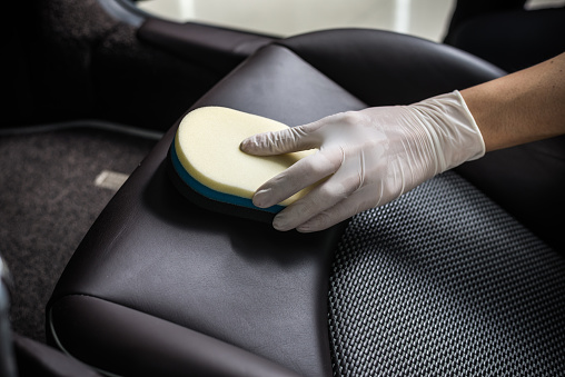 Gloved hand cleaning car seat with sponge.