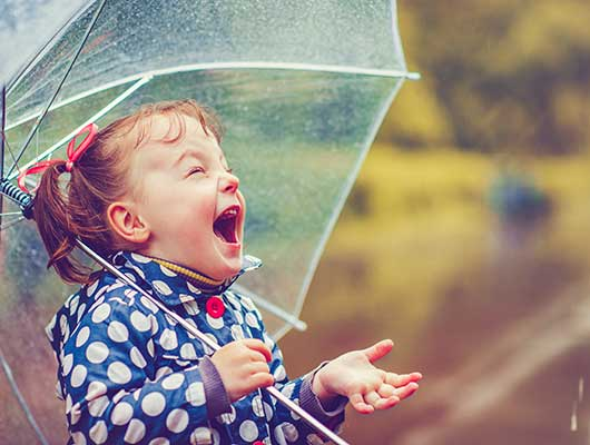 Little girl enjoying the rain.